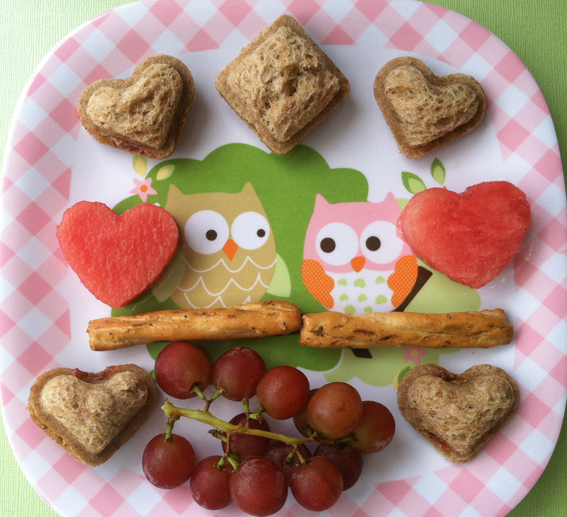 Vegan lunch owls are sitting on 2 Snyder's braided whole grain pretzel sticks